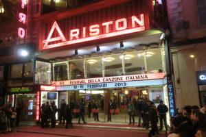 Aufnahme des Ariston-Theaters in Sanremo an einem Abende des Festivals 2013. Zuschauer sind außerhalb der Absperrungen zu sehen, während sich im Eingangsbereich Sicherheitskräfte aufhalten.